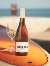 Bottle of Nielson SBC Chardonnay sitting on top of a surf board on the each