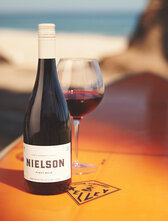 Bottle of Nielson SBC Pinot Noir sitting on top of a surf board on the beach