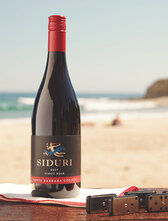 Bottle of Siduri SBC Pinot Noir sitting on a table on the beach with Dominoes next to it