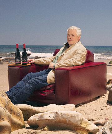 Siduri Wines winemaker, Adam Lee, sitting on the beach with wine