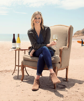 Cambria winemaker, Jill Russel, sitting on the beach holding glass of wine
